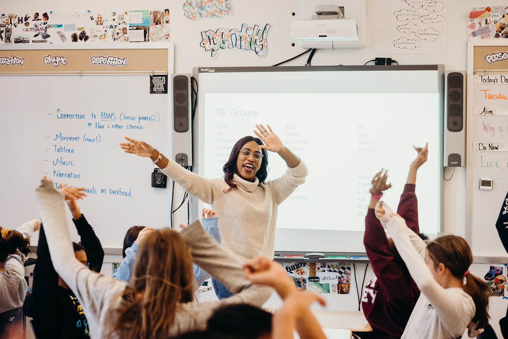 A teacher leads a class warm-up in a Focus Schools classroom.
